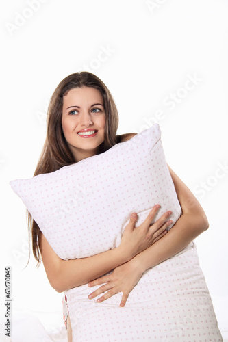 Smiling young woman embraces her pillow