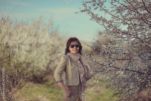 woman in trousers with a scarf garden flowering trees