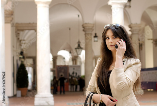 young girl at phone in an elegant palace interior