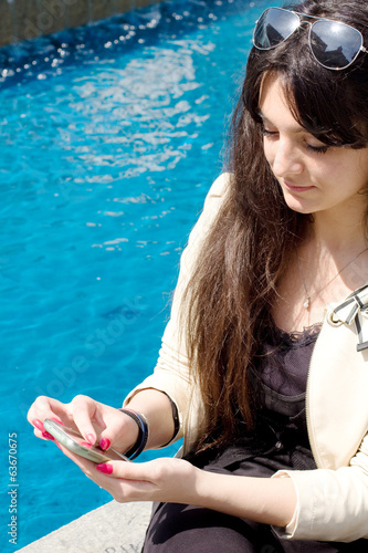 young girl with long black hair with smart phone