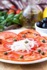 Fresh healthy tomato carpaccio with capers, balsamic vinegar, ol