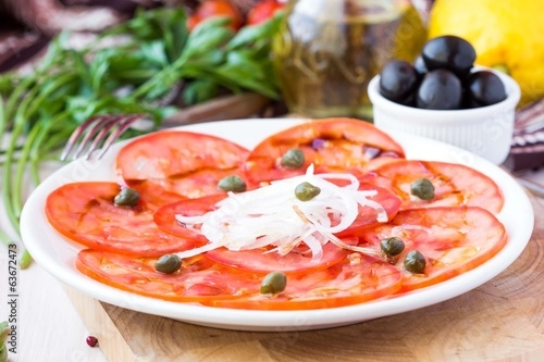Fresh healthy tomato carpaccio with capers, balsamic vinegar, ol