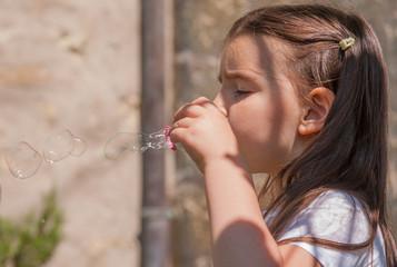 Concentrazione nel gioco bolle di sapone all'aria aperta
