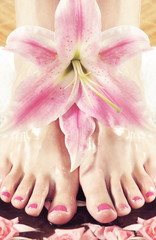 Spa background with beautiful legs and flowers