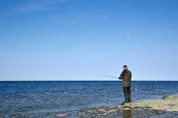 Man fishing at a flat rock coast