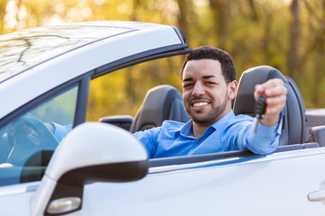 Young black latin american driver holding car keys driving his n