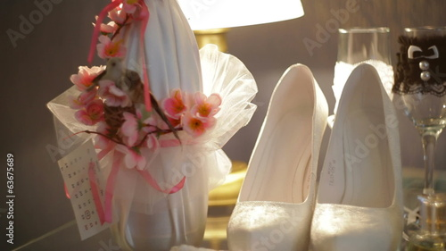 Beautiful white bridal shoes and a bottle of champagne