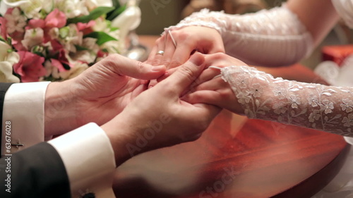 Bride and groom holding each other's hands at the table