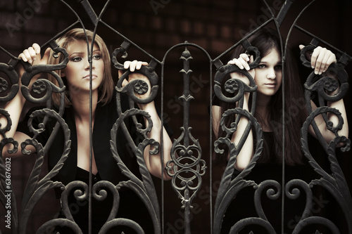Two sad young women at the iron fence