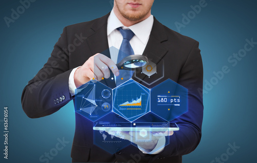 businessman hand holding magnifier over tablet pc