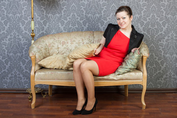 young sexy woman sits on a sofa
