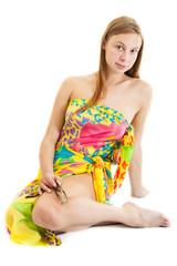 sensual blonde girl wearing a bright pareo sits