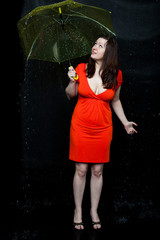 Young woman wearing red dress stands under an umbrella