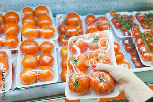 Packaged tomato with woman hand in the supermarket