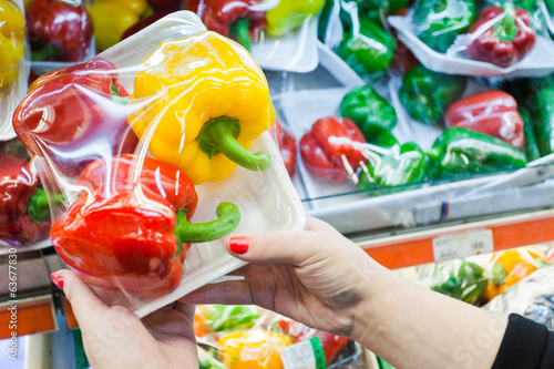 Packaged bell pepper with woman hand in the supermarket