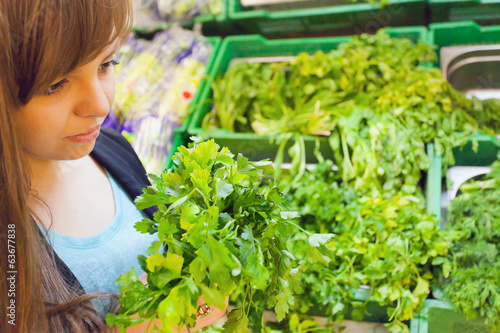 Green parsley with woman hand in the supermarket