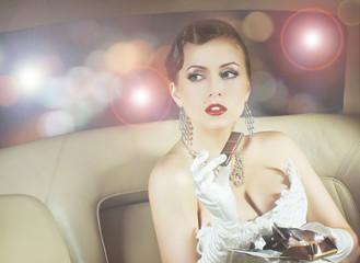 Beautiful celebrity woman sitting in a luxury car