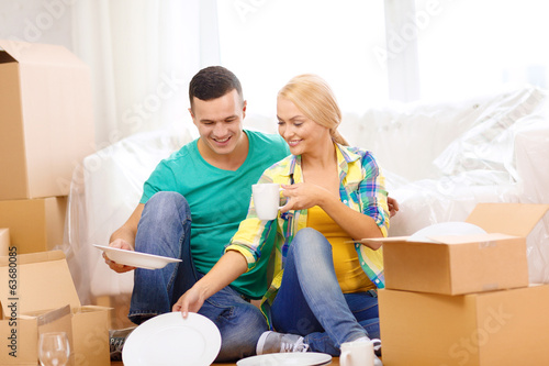 smiling couple unpaking boxes with kitchenware