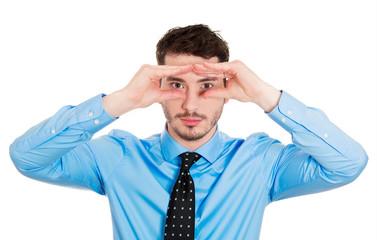 Young curious business man looking through binoculars