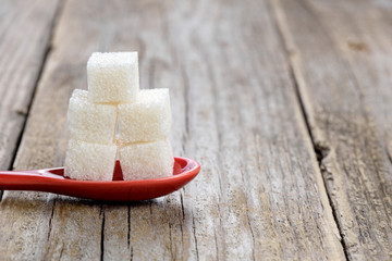 Sugar cubes in spoon on wooden background