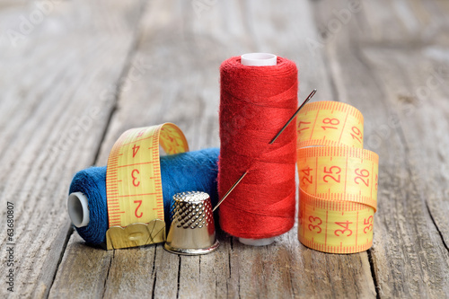 Spools of thread, needle, measuring tape and thimble