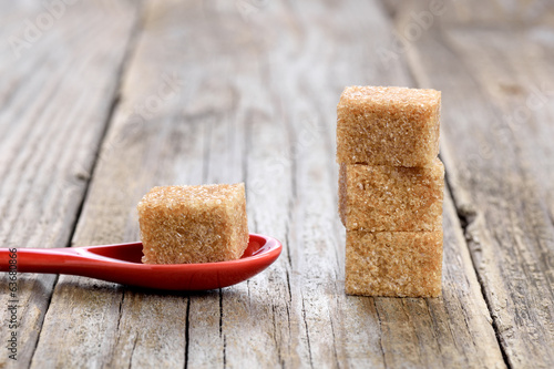 Cane sugar cubes in spoon on wooden background