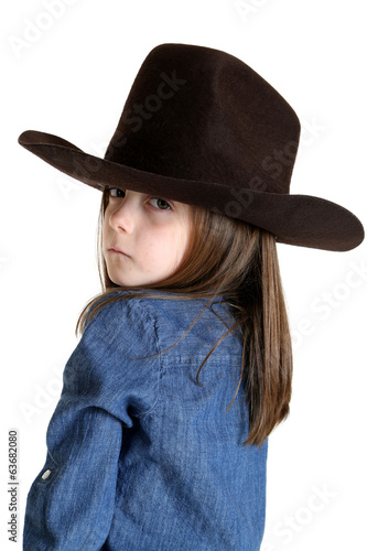 young cowgirl looking over her shoulder with a tough look