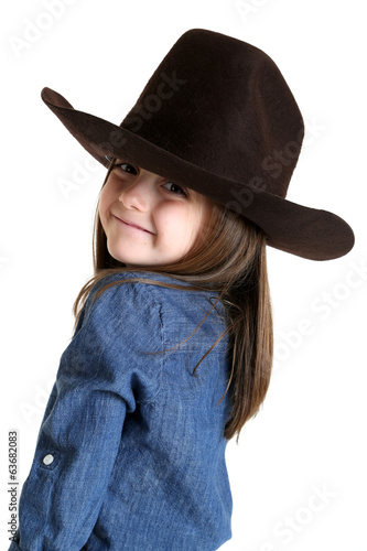 Cute young cowgirl looking over her shoulder smiling