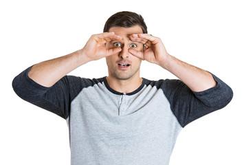 Surprised young man looking through hand binoculars