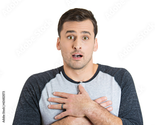 Surprised young man hands on chest