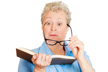 Old woman in glasses having difficulties to read a book
