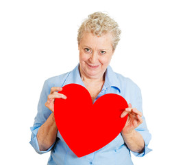 Older woman in love, holding red heart, on white background