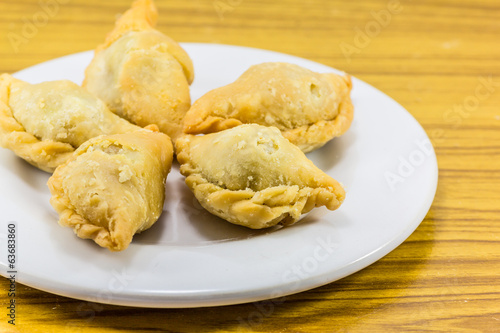 Five curry puffs on white plate