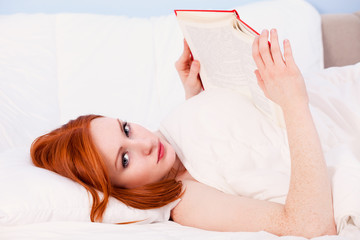 young woman reading in her bed