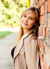 relaxation in the city, beautiful girl near brick wall, smilin