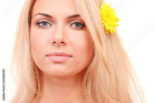 Beautiful young woman with a bright flower in her hair