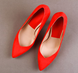 Beautiful red female shoes, on grey background