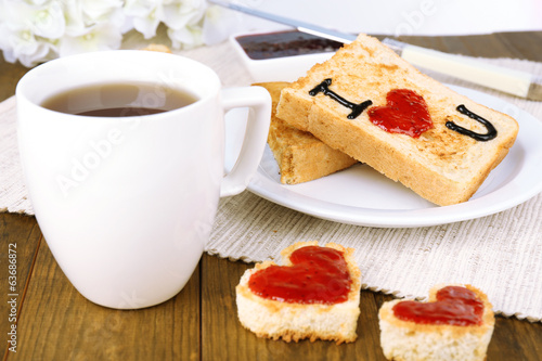 Delicious toast with jam and cup of tea on table close-up