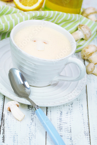 Delicate mushroom sauce in cup on wooden table close-up