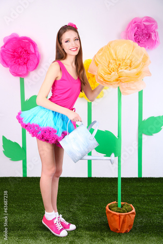 Beautiful young woman in petty skirt watering flower
