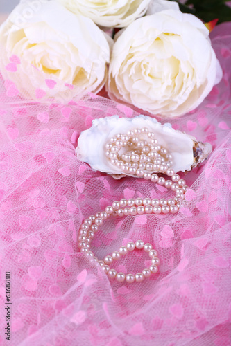 Beautiful pearls in shell on pink cloth