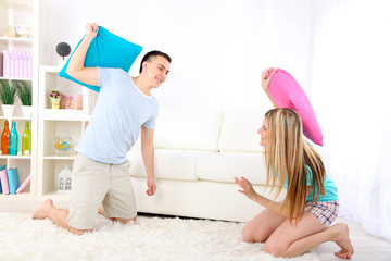Couple fighting together with pillows