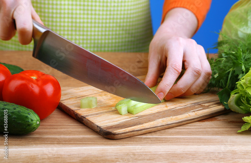 Female hands cutting celery