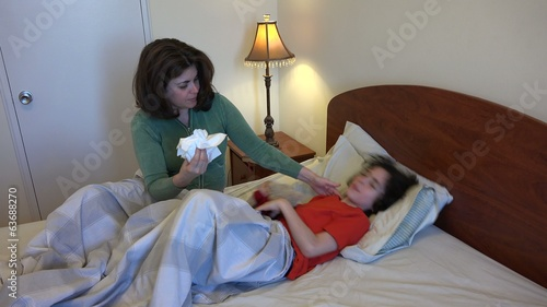 Single mother or parent taking care of her sick son