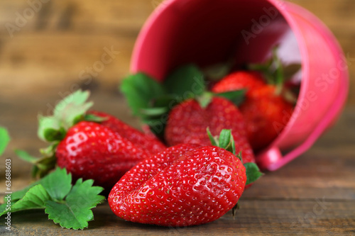 Strawberries with in decorative bucket on wooden background