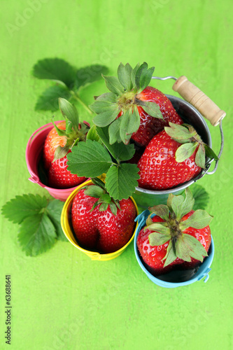 Strawberries with in decorative buckets on wooden background