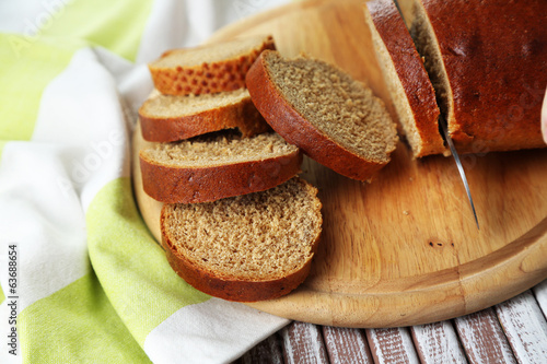 Female hands cutting bread on wooden board, close-up