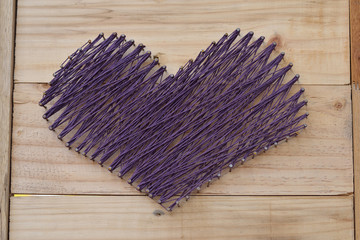 yarn shape of heart on wooden board background