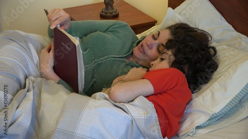 Single mother reading the Bible to her son