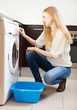 long-haired woman doing laundry with washing machine